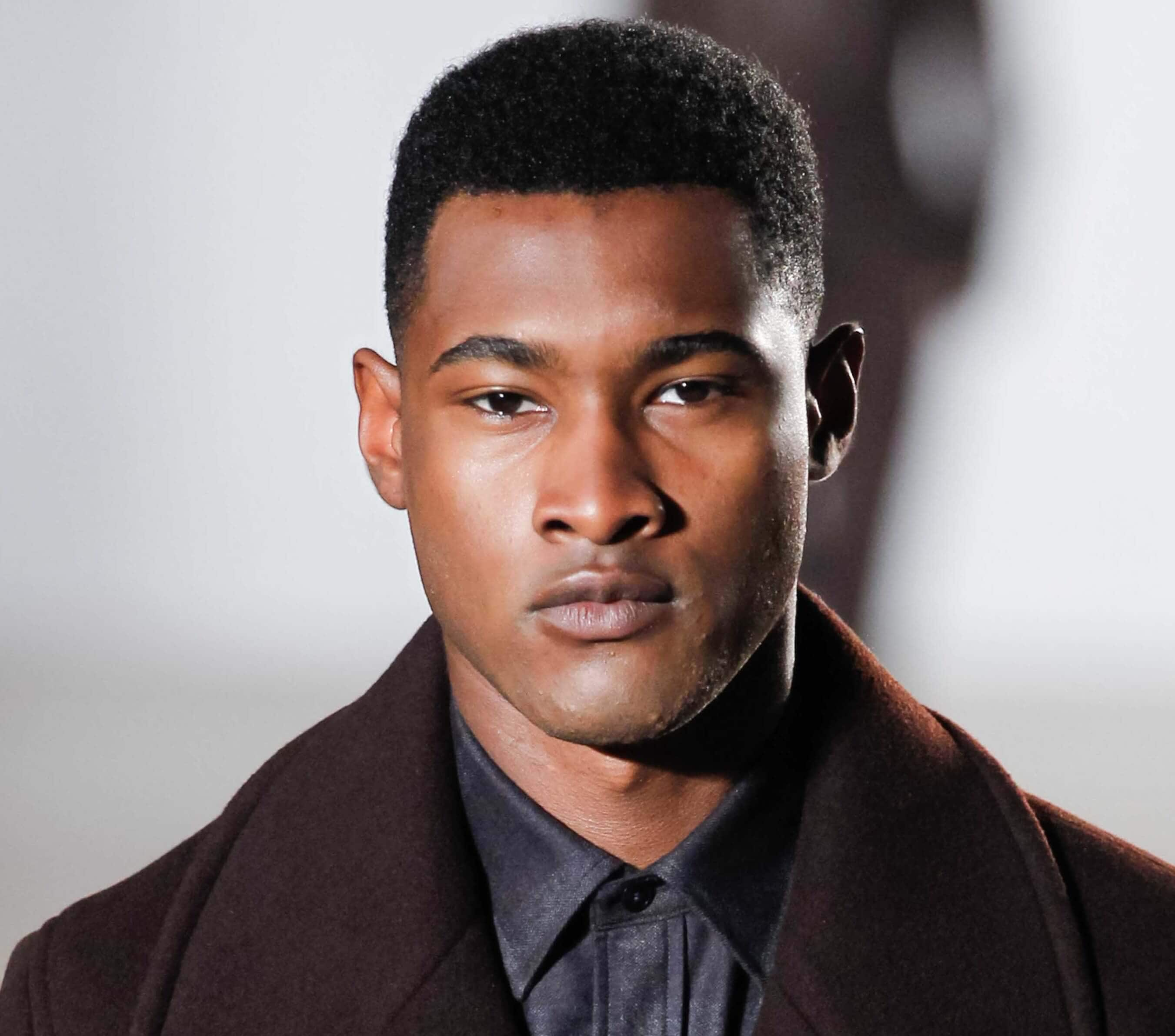 High top fade: Black man on runway with short high top fade wearing dark outfit.