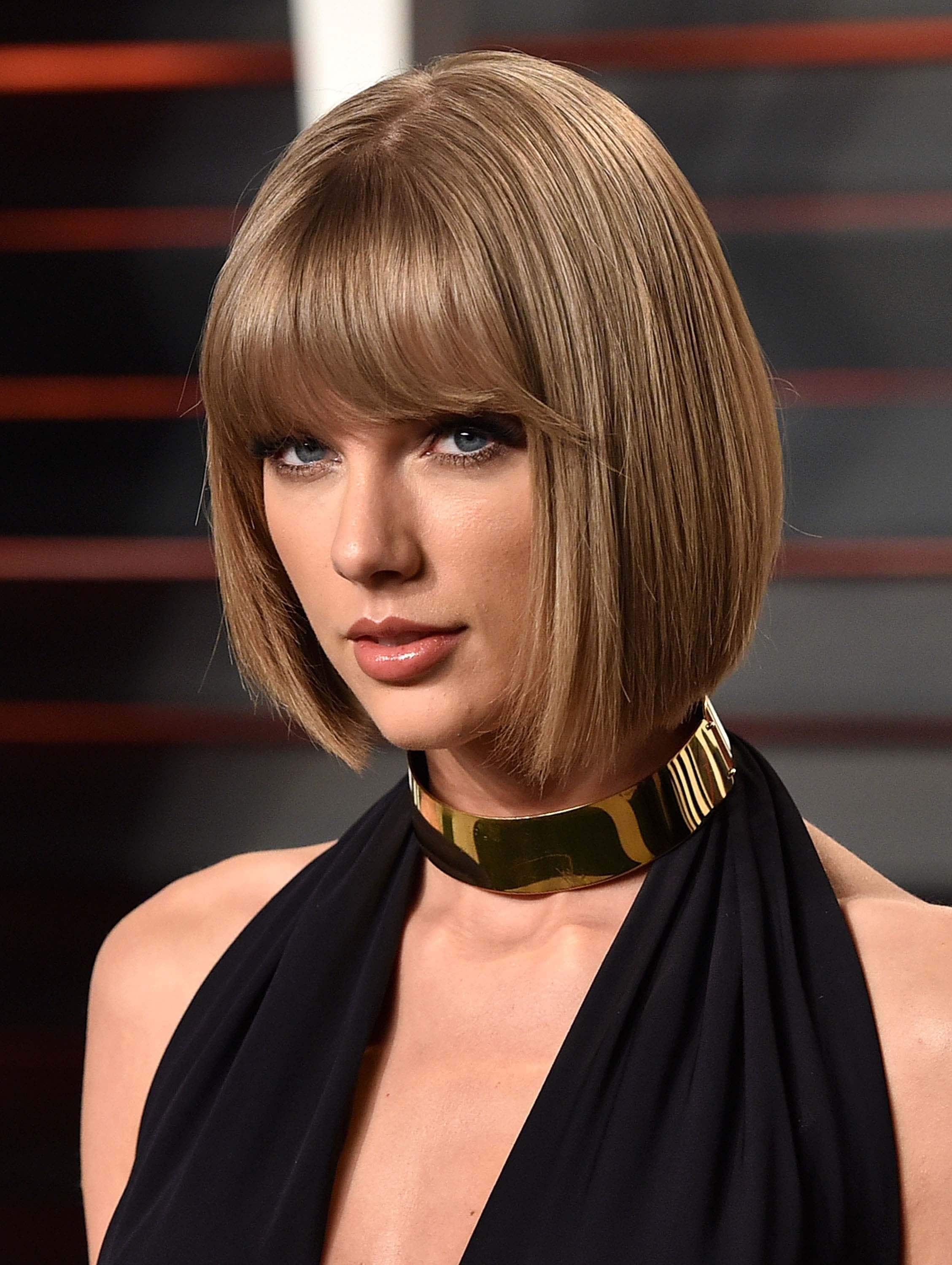 close up shot of taylor swift short bob with blunt bangs, wearing black dress with gold necklace on the red carpet