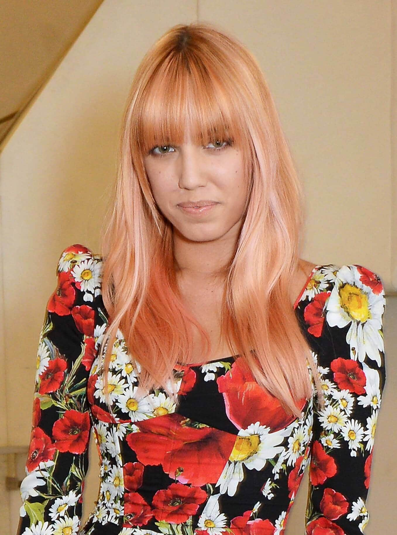 close up shot of amber le bon with pink hair and blunt feathery bangs, wearing floral dress and posing backstage