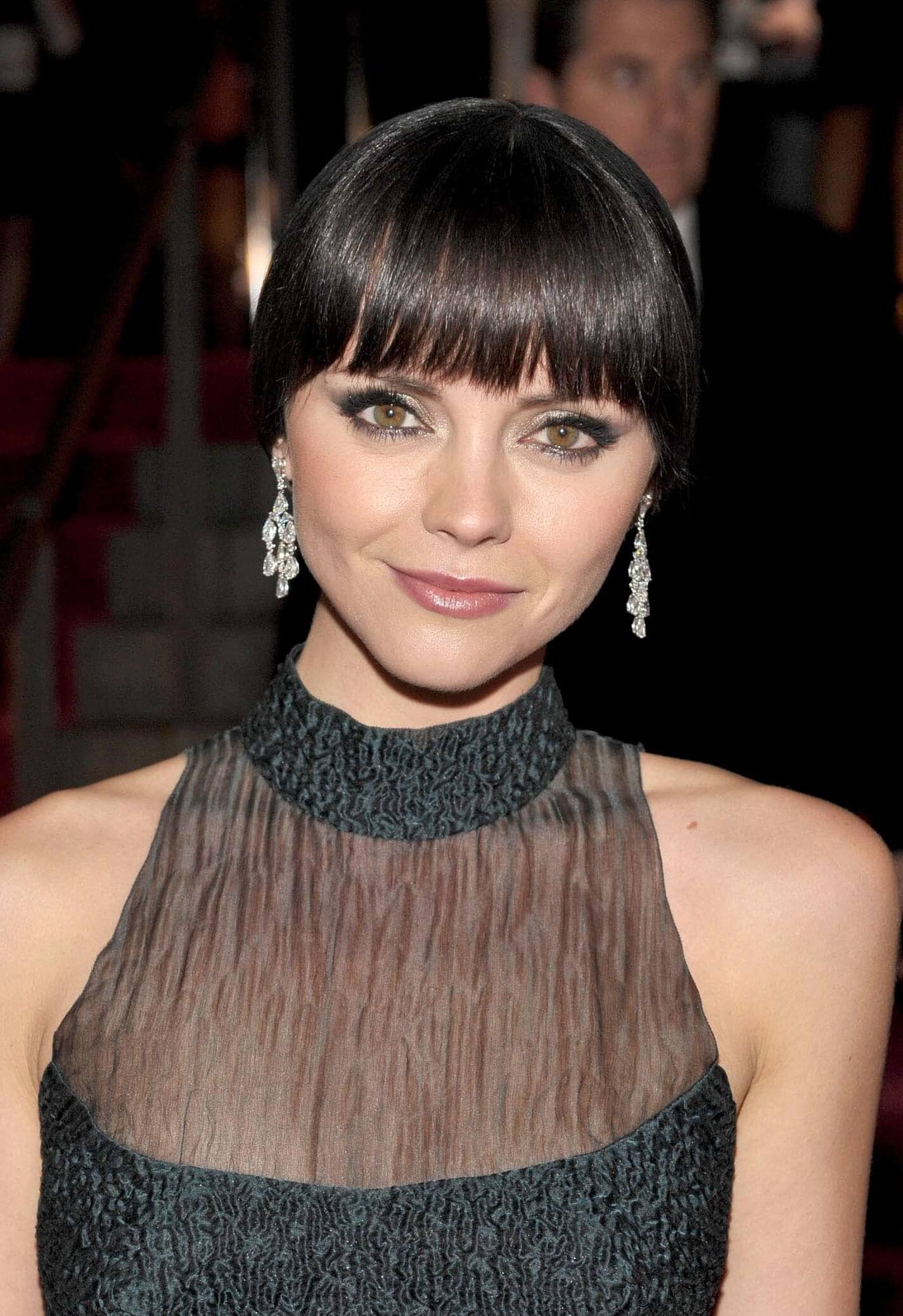 close up shot of christina ricci with blunt bang hairstyle that has wispy ends, wearing statement earrings and black sheer top on the red carpet