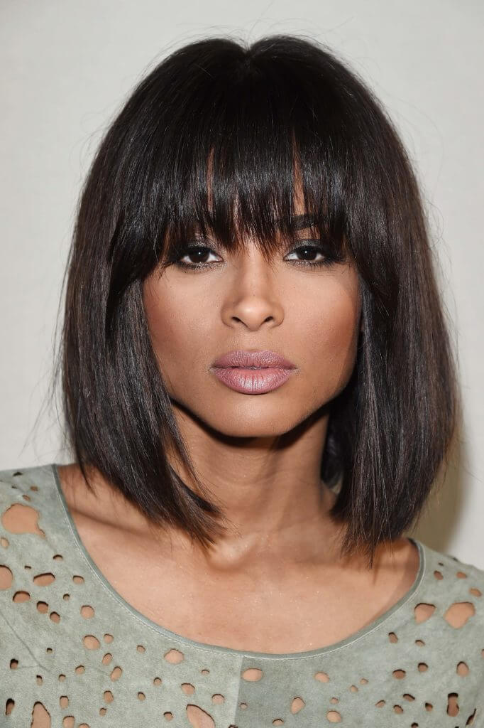 close up shot of ciara with wispy blunt bangs and long bob hairstyle, wearing green top and posing on red carpet