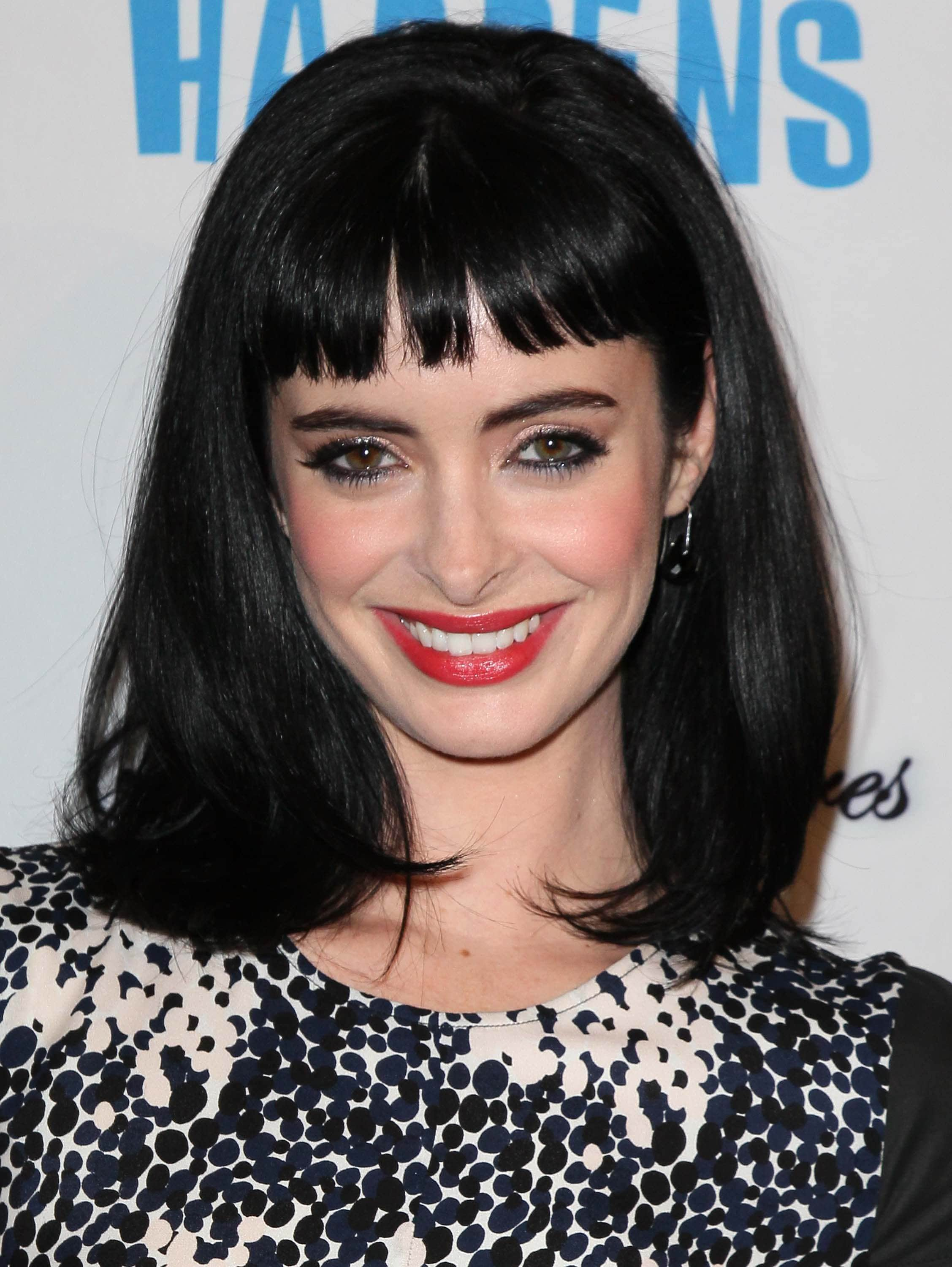 close up shot of Krysten Ritter with bettie page-inspired fringe hairstyle, wearing blue and black dress and posing on the red carpet