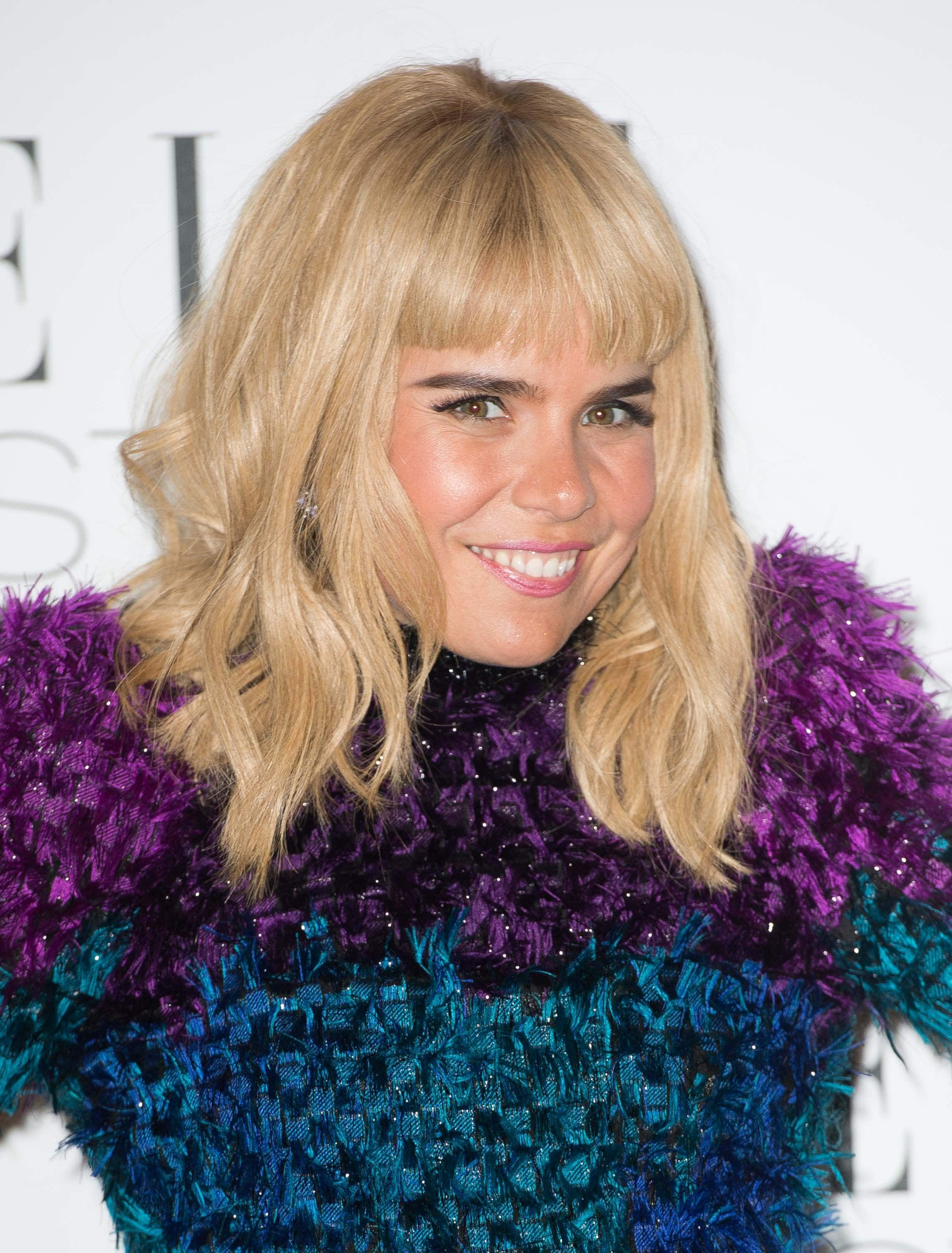 close up shot of paloma faith with messy blonde hair and feathery blunt bangs, wearing blue and purple dress on the red carpet