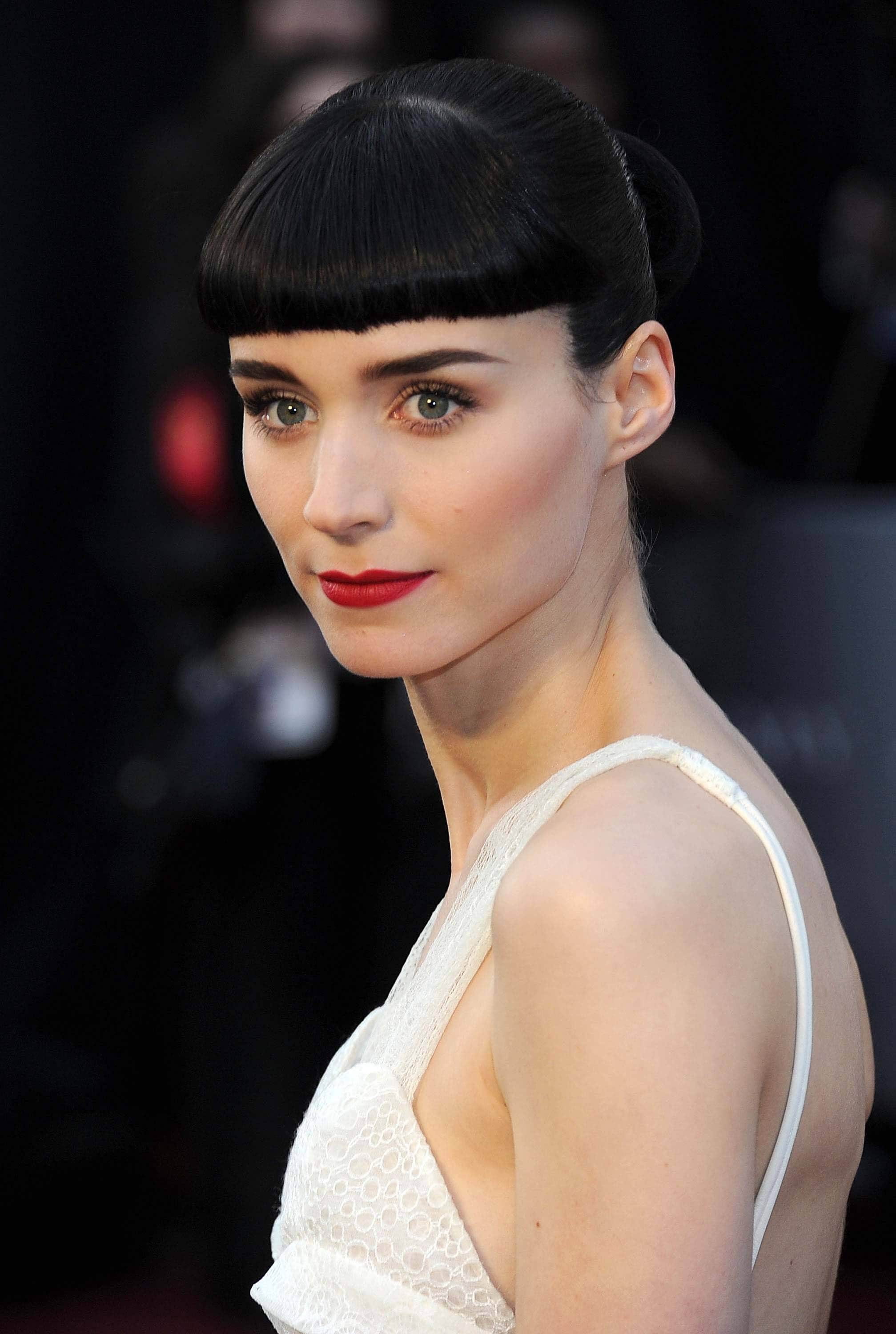 close up shot of rooney mara with blunt bangs and bun hairstyle, wearing red lipstick and white dress on the red carpet