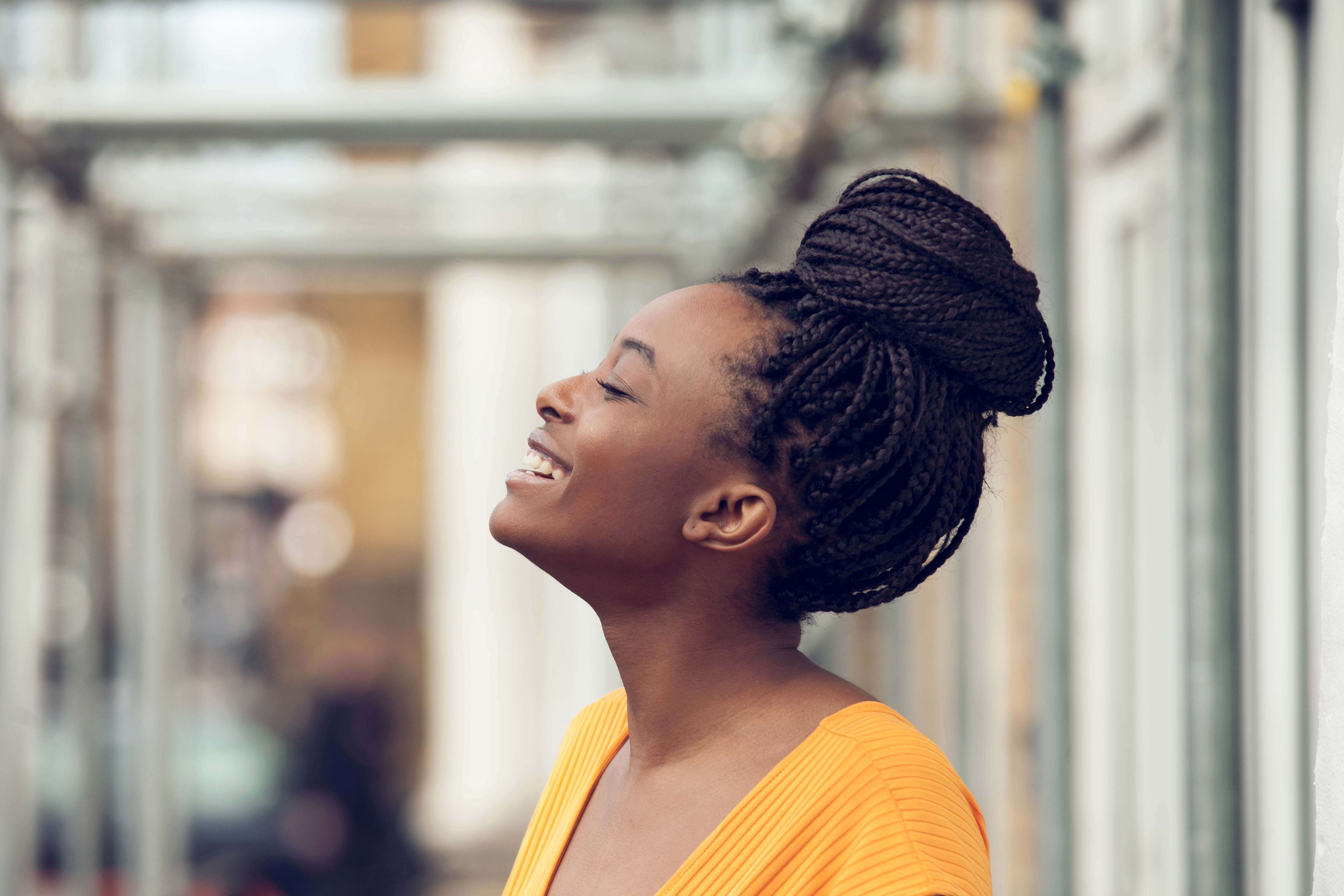 hairstyles for box braids: laughing young black woman with box braids in a high bun