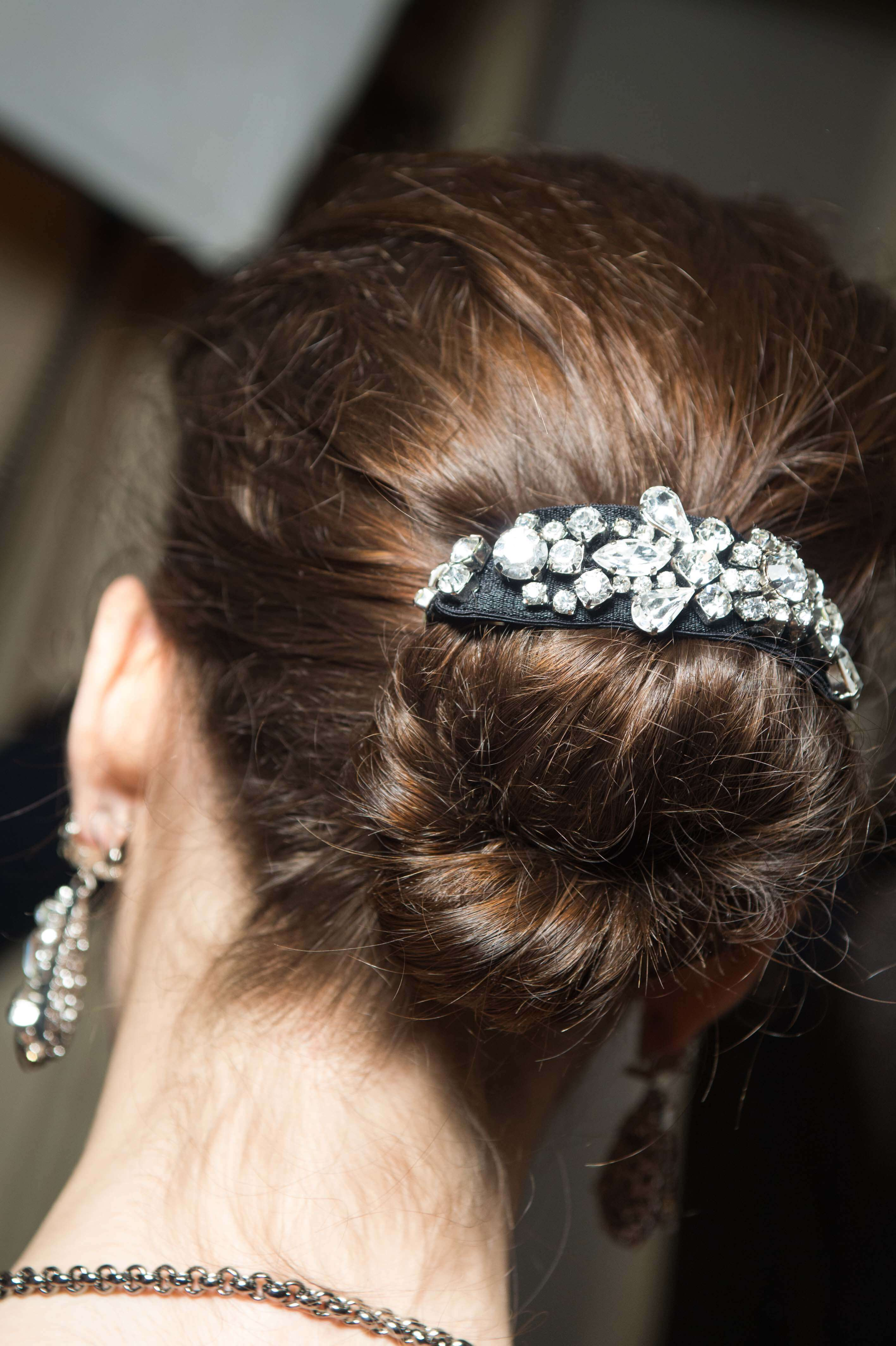 back view of a brunette with her hair in a messy bun with a jewelled bun cuff