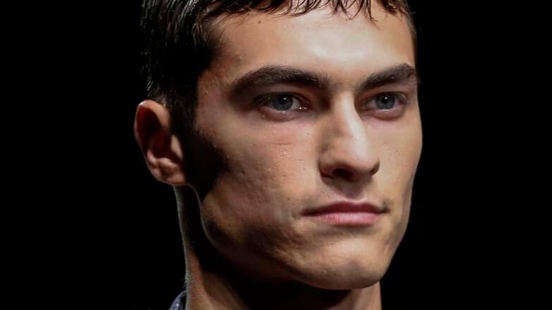 Dark haired male model with a wet-look Caesar haircut