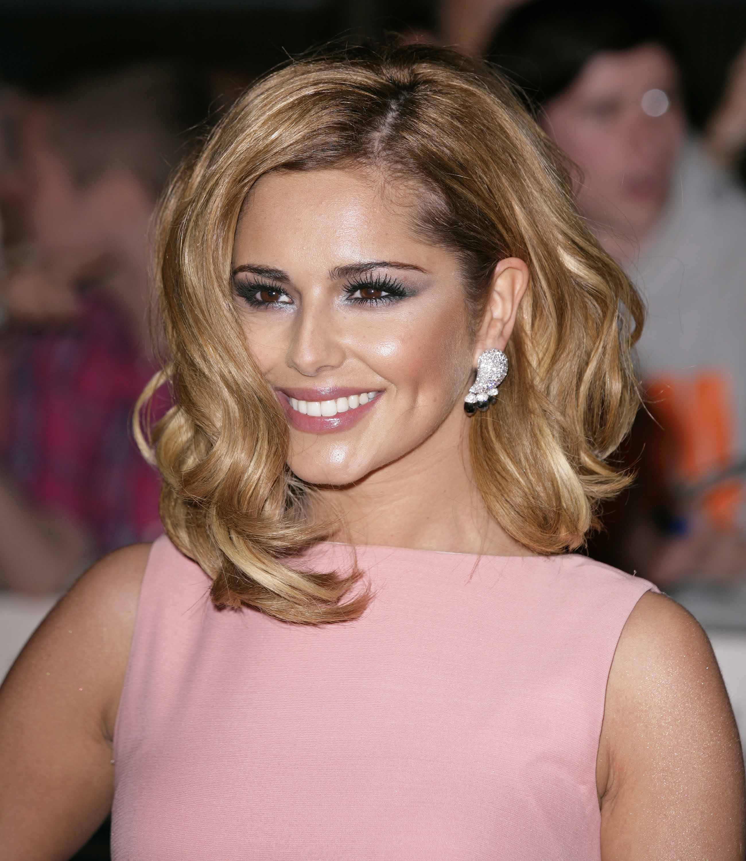 Brown hair with highlights: Cheryl Tweedy with curly warm bronde highlighted hair, wearing a pink dress