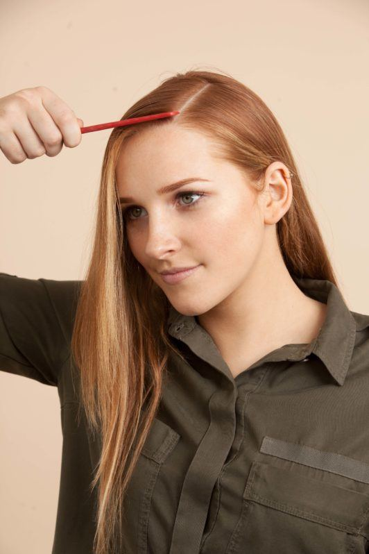 a beautiful woman combing her long red hair