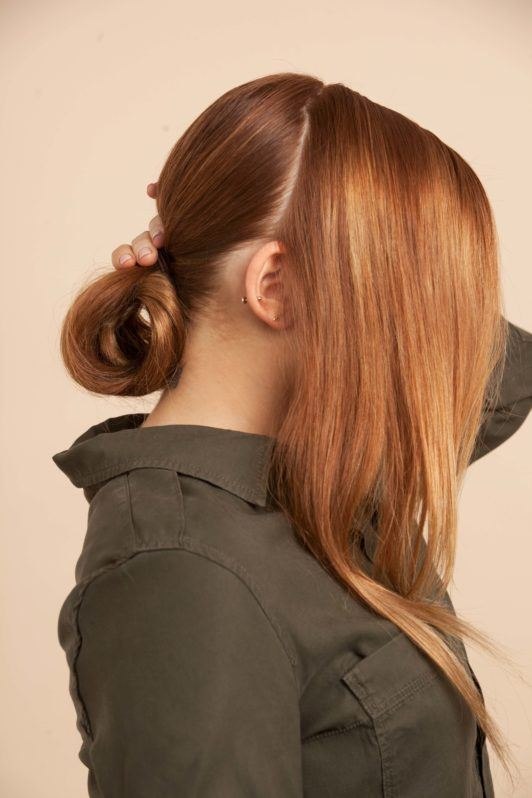 a chignon bun of a woman side view on pink background