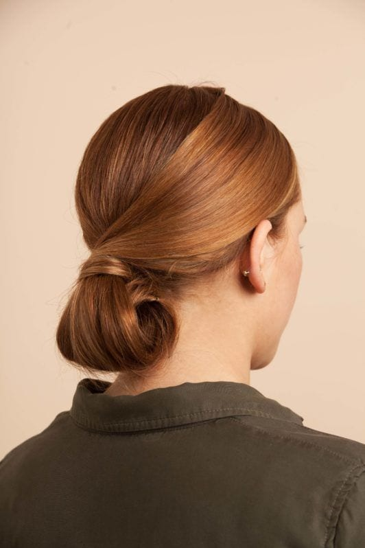 a woman with perfect chignon bun on the pink background