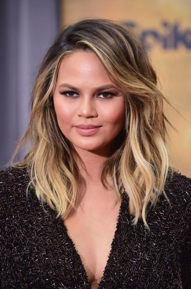 Brown hair with blonde highlights: Chrissy Teigen with wavy sunkissed blonde shoulder length hair