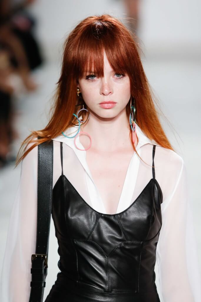 model on the runway with a ronze copper hair dye and a long fringe