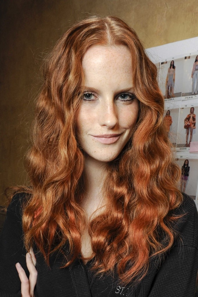 model with long loose waves and dark rose tinted copper hair