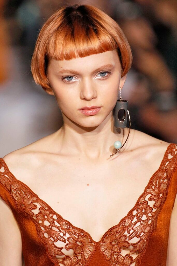 model on the runway with a bob and blunt fringe with an intense rose gold copper hair