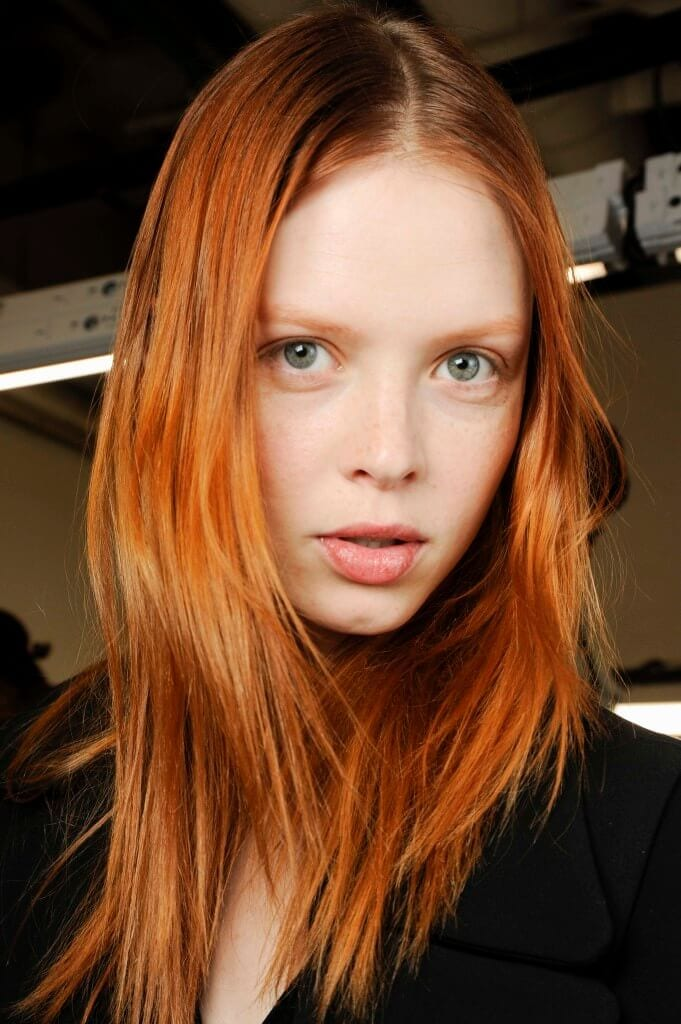 model backstage at fashion show with warm copper red hair