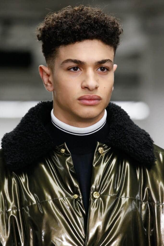 High top fade: Man on runway with natural afro high top hairstyle wearing a shiny jacket.