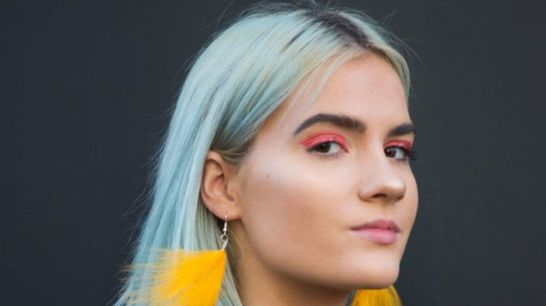 Does dyeing your hair damage it: Woman with sky blue hair, wearing yellow fluffy earrings with furry jacket posing for a street style shot