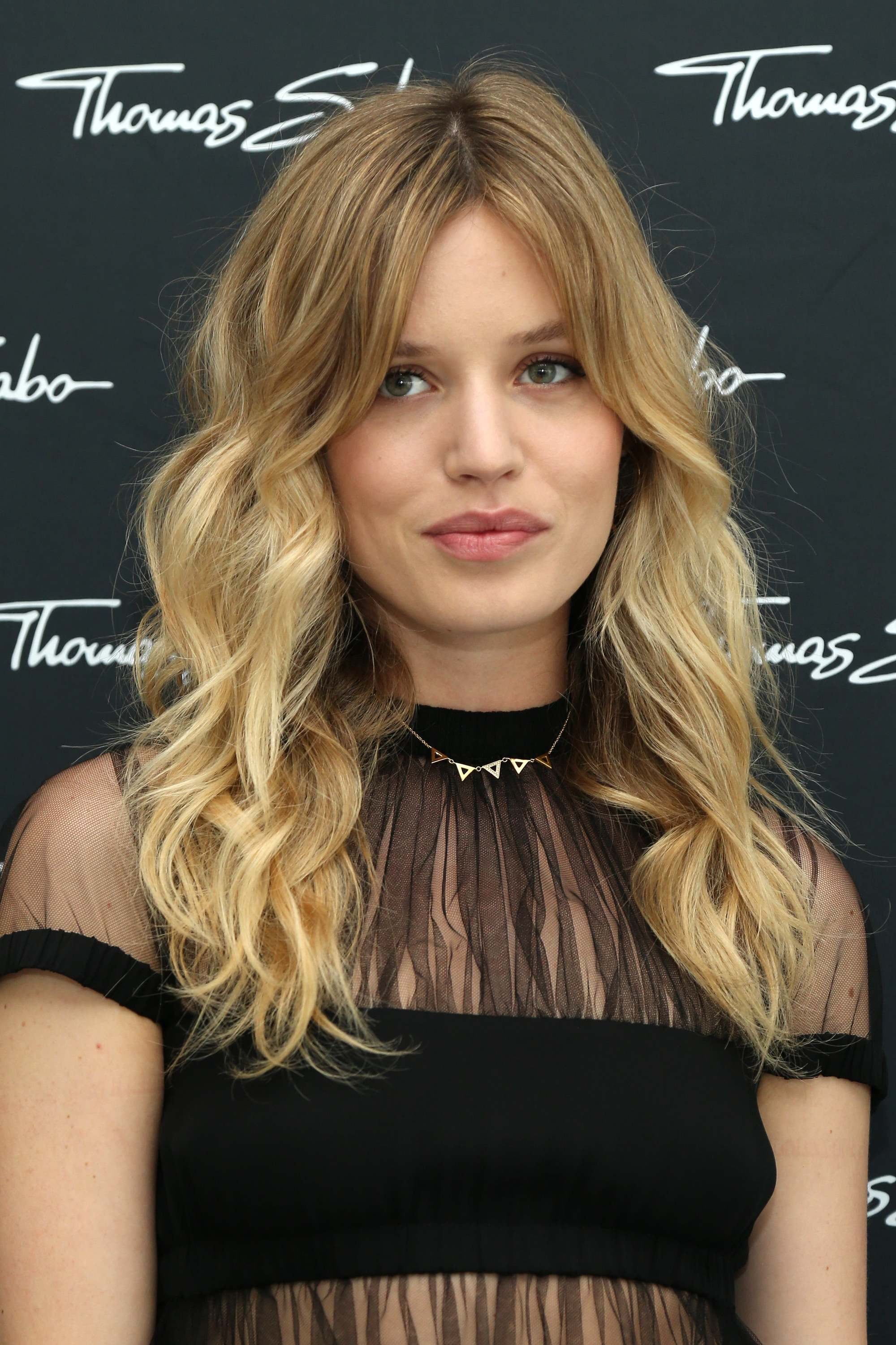 Brown hair with blonde highlights: Georgia May Jagger with sandy blonde curly hair with split Bardot bangs, wearing a black sheer lace top