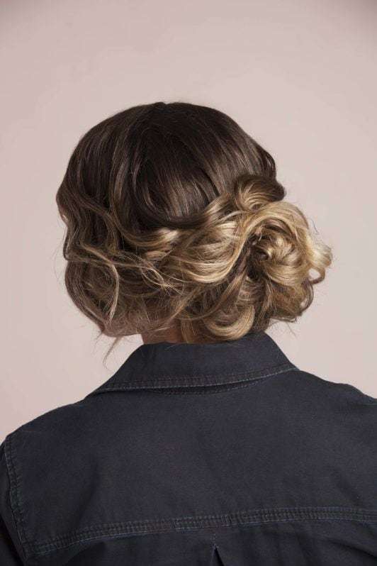 Messy bun: Back view of a brunette woman with a curly bun updo