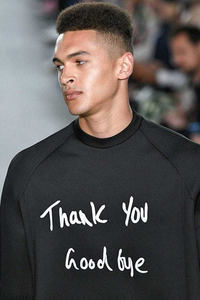 High top fade: Man on runway with high top haircut wearing a slogan jumper