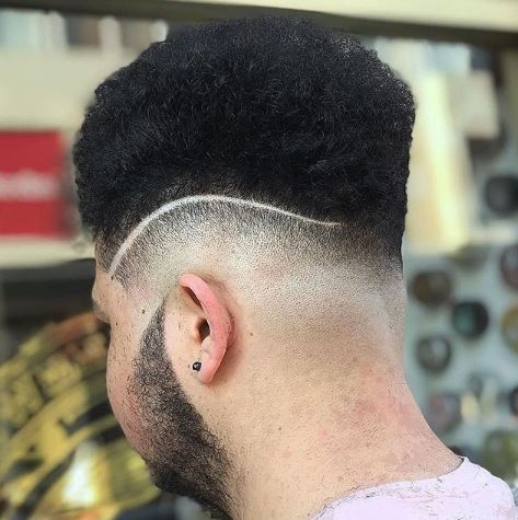 High top fade: Man with shaved curve design on side of his head with a high top.