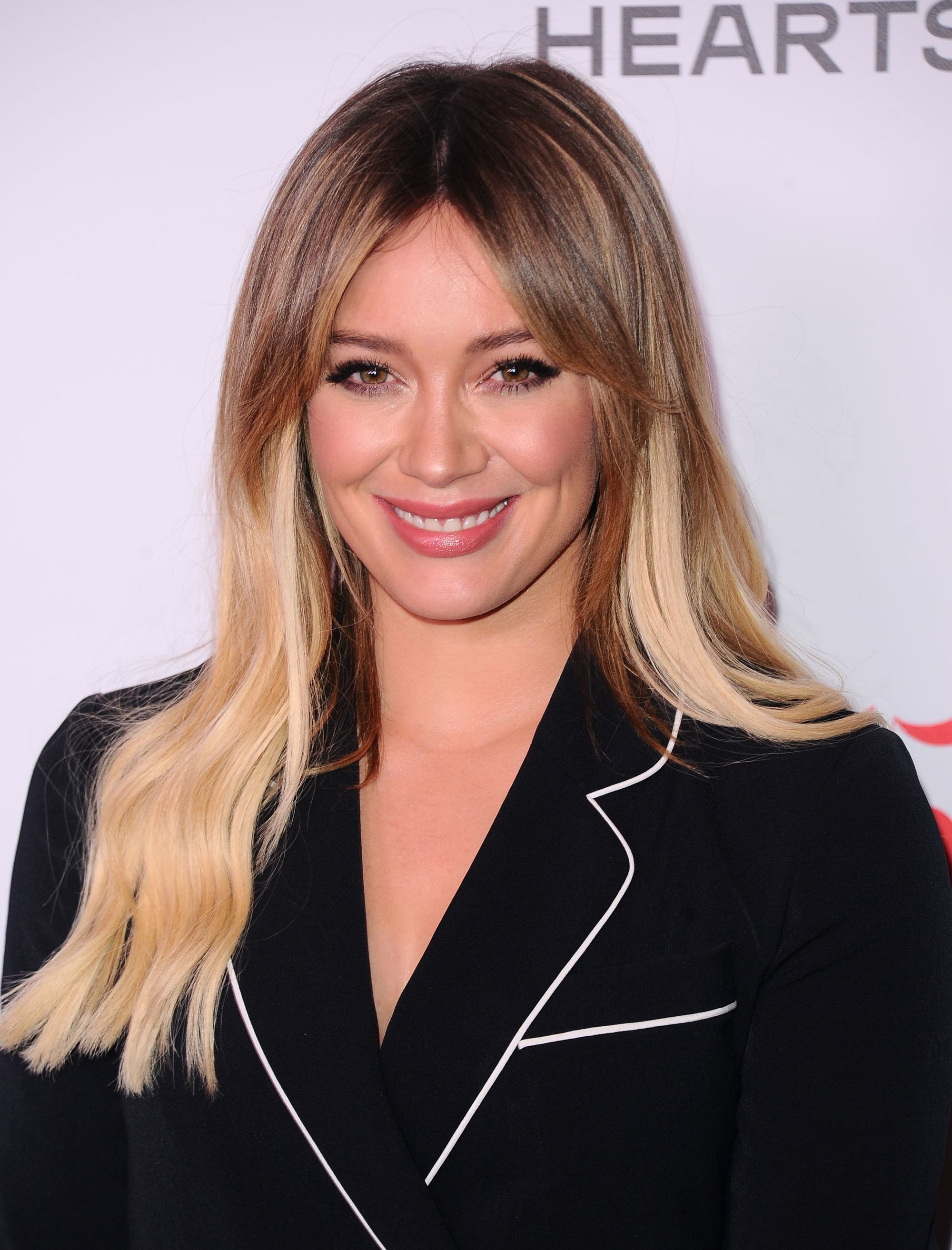 Brown hair with blonde highlights: Hilary Duff with long brunette and blonde balayage hair, wearing a black blazer