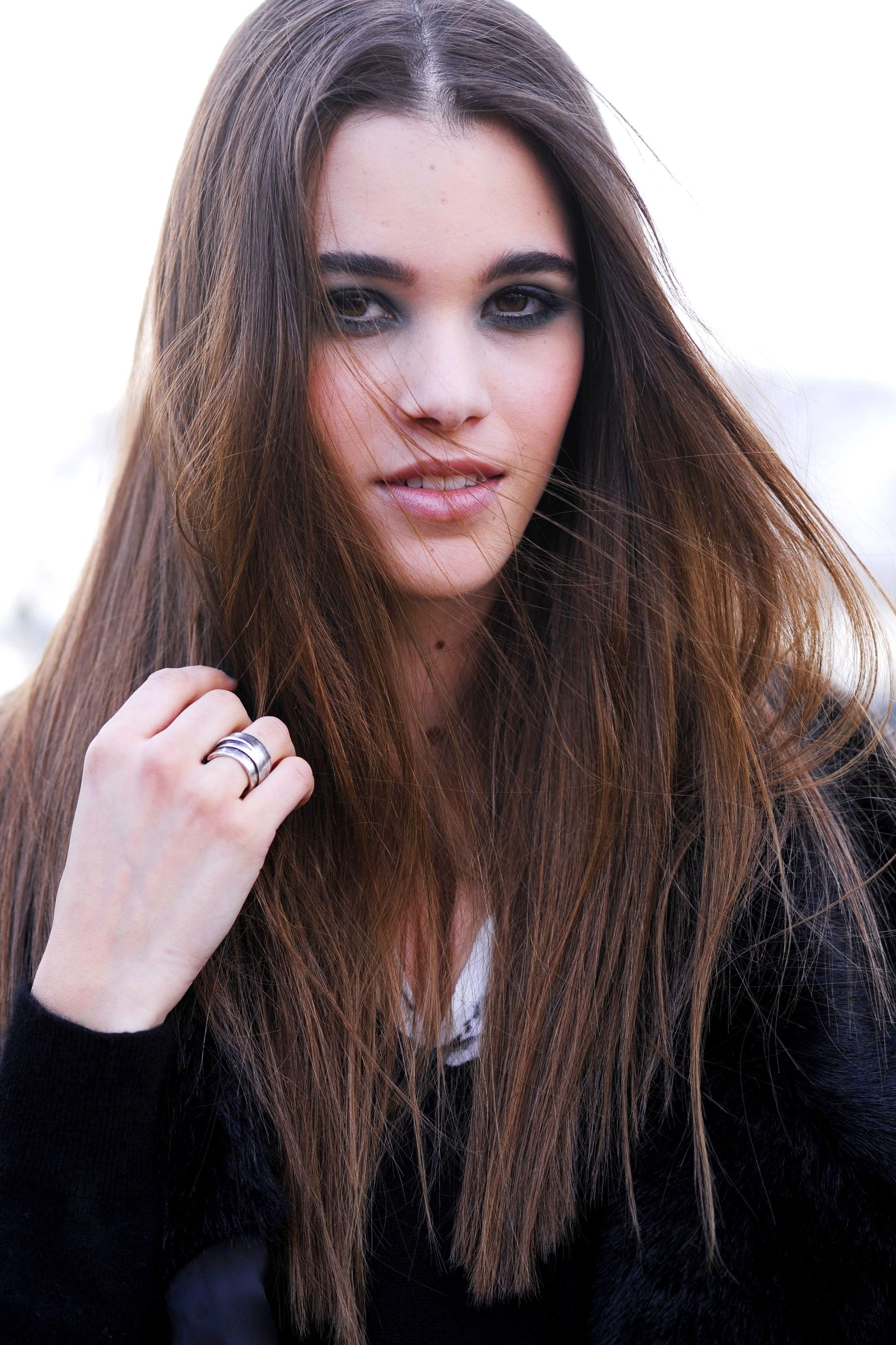 Hot oil treatment hair guide: Woman with long, healthy dark brown hair wearing a black jacket outside
