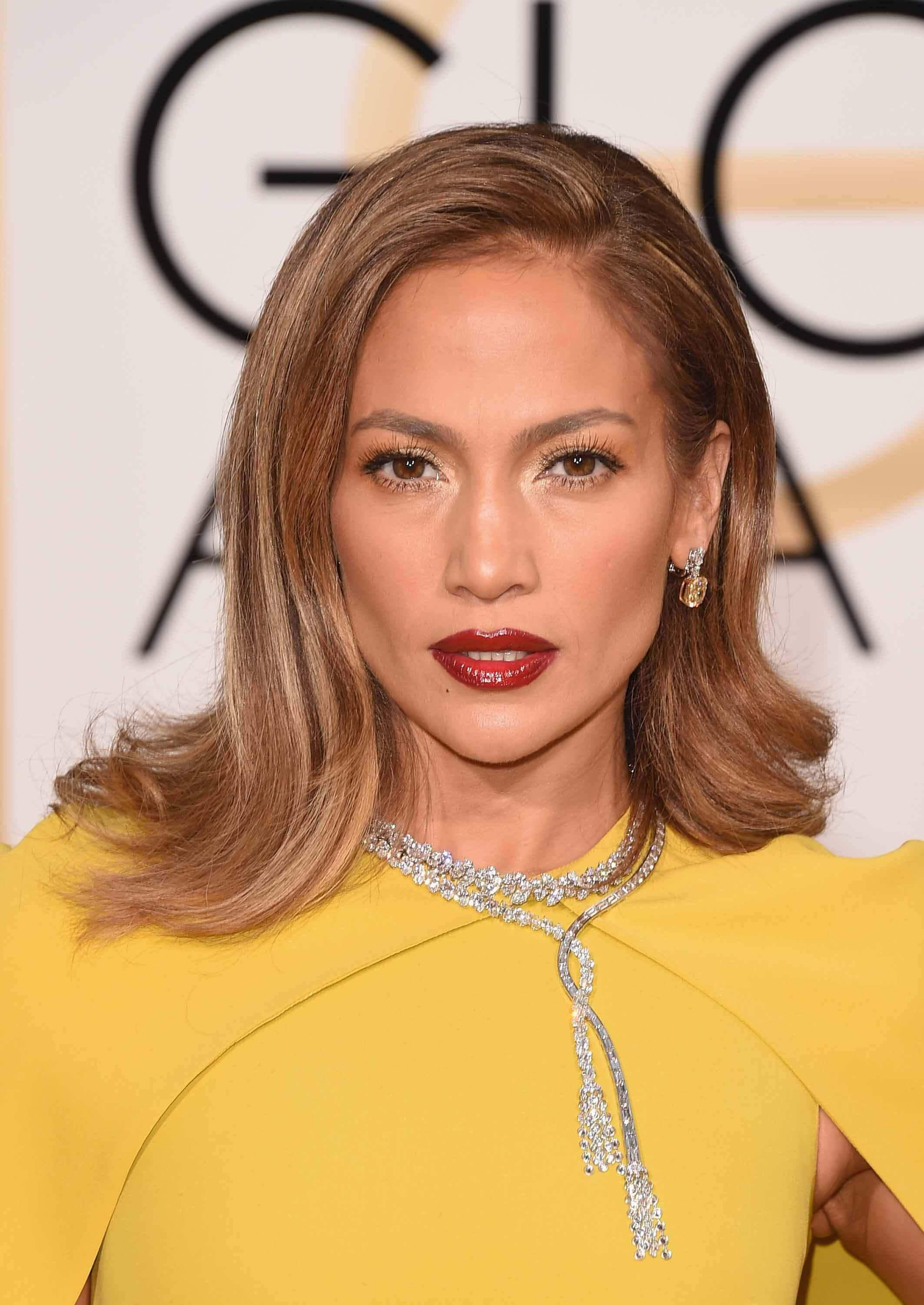 Brown hair with highlights: Jennifer Lopez with brown hair with highlights wearing a yellow dress on the red carpet
