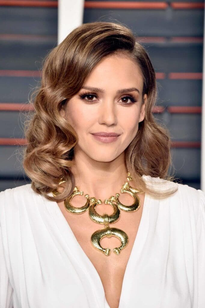 Jessica Alba with brown hair with highlights wearing a chunky gold necklace and a white dress