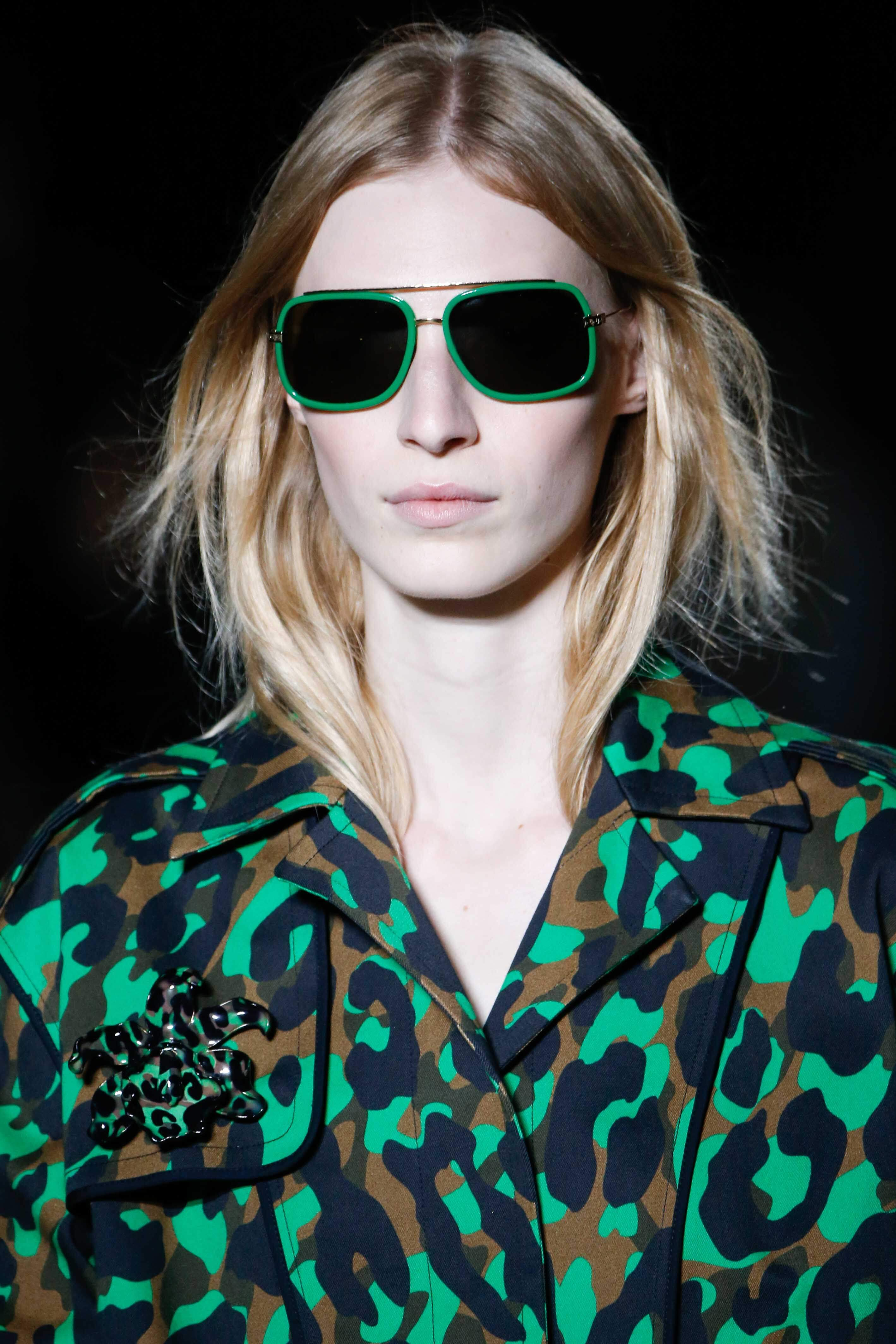 Blonde hair: Front facing view of a woman wearing green sunglasses with ash blonde hair colour.
