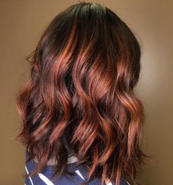 woman with a subtle copper hair colour mixed with her naturally dark hair