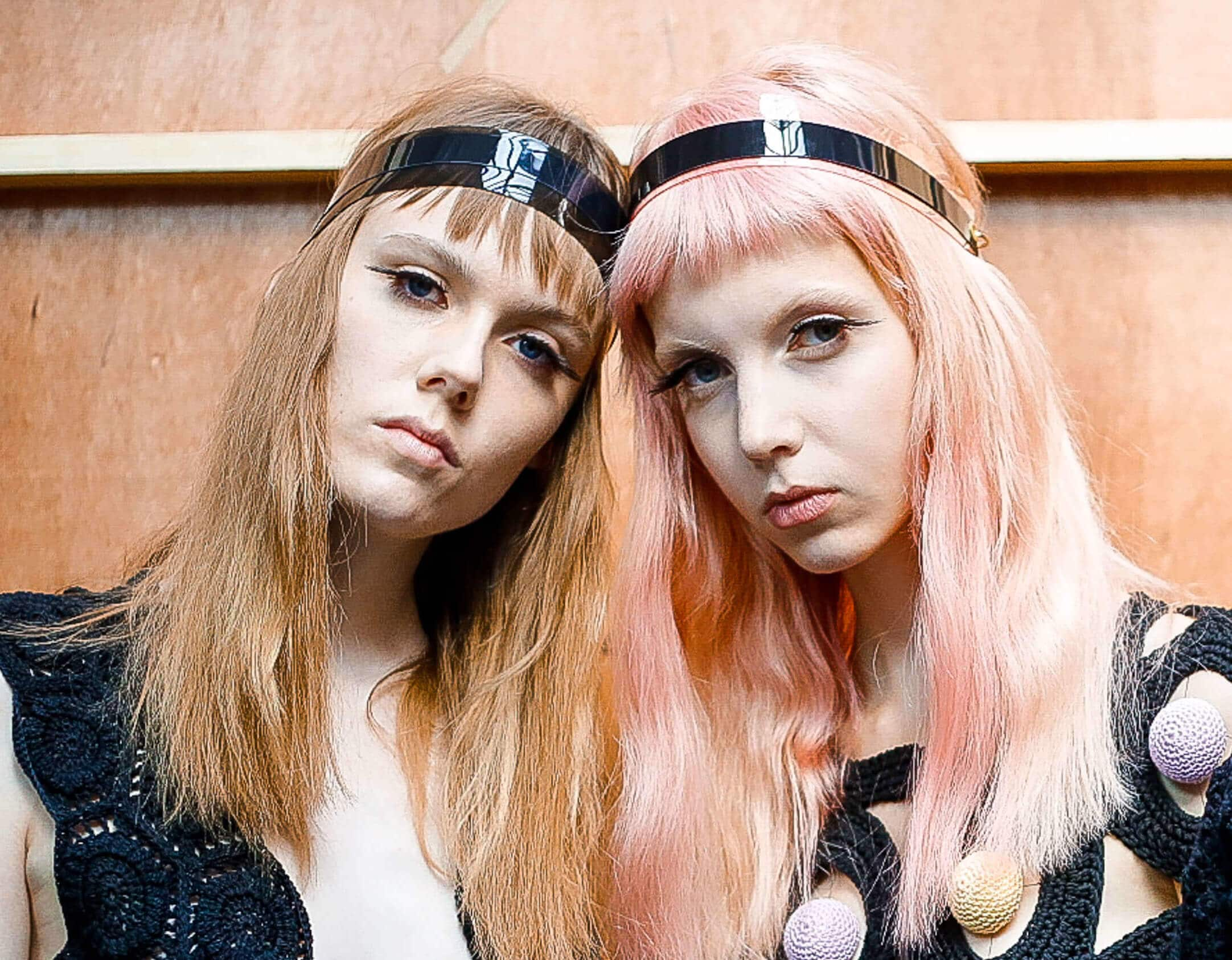 Silver shampoo: Backstage fashion week shot of two models, one with light brown hair and one with pink, both wearing black headbands.