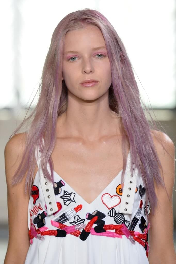 a female fashion mode with lavender hair walking on the runway