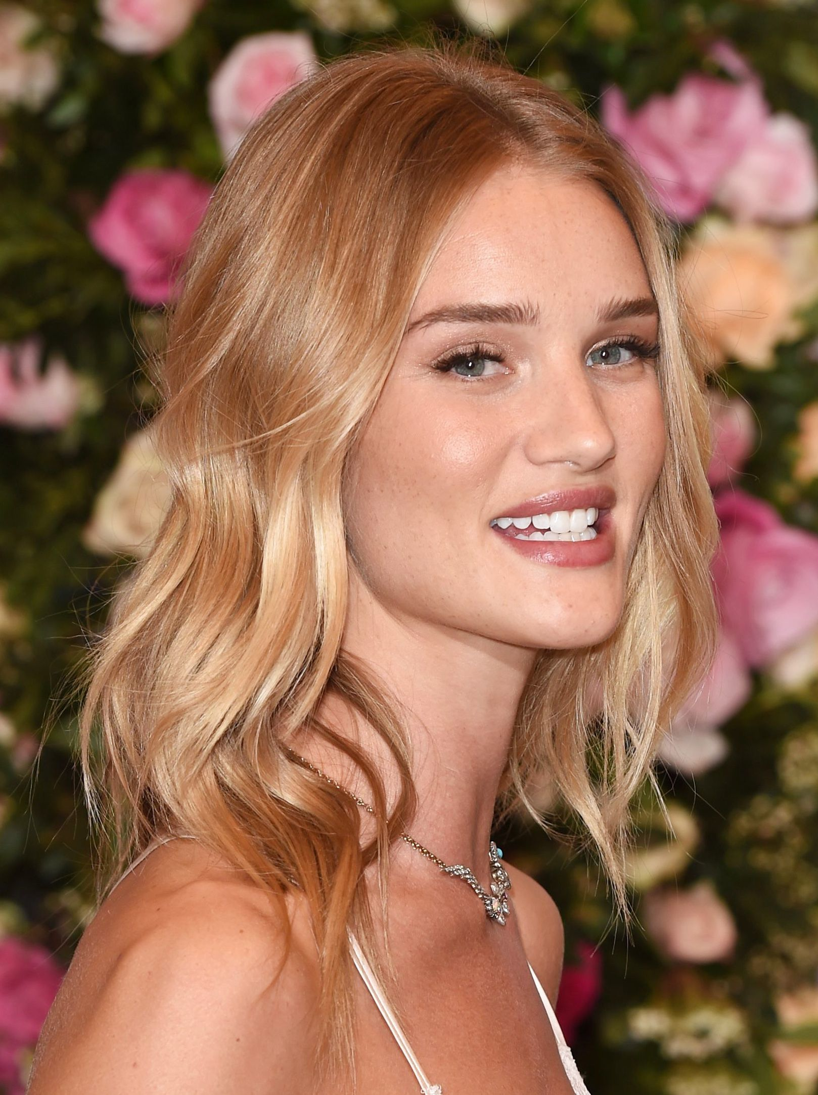 Brown hair with blonde highlights: Rosie Huntington-Whitely with strawberry blonde highlighted shoulder length hair in soft curls, standing against a wall of pink flowers