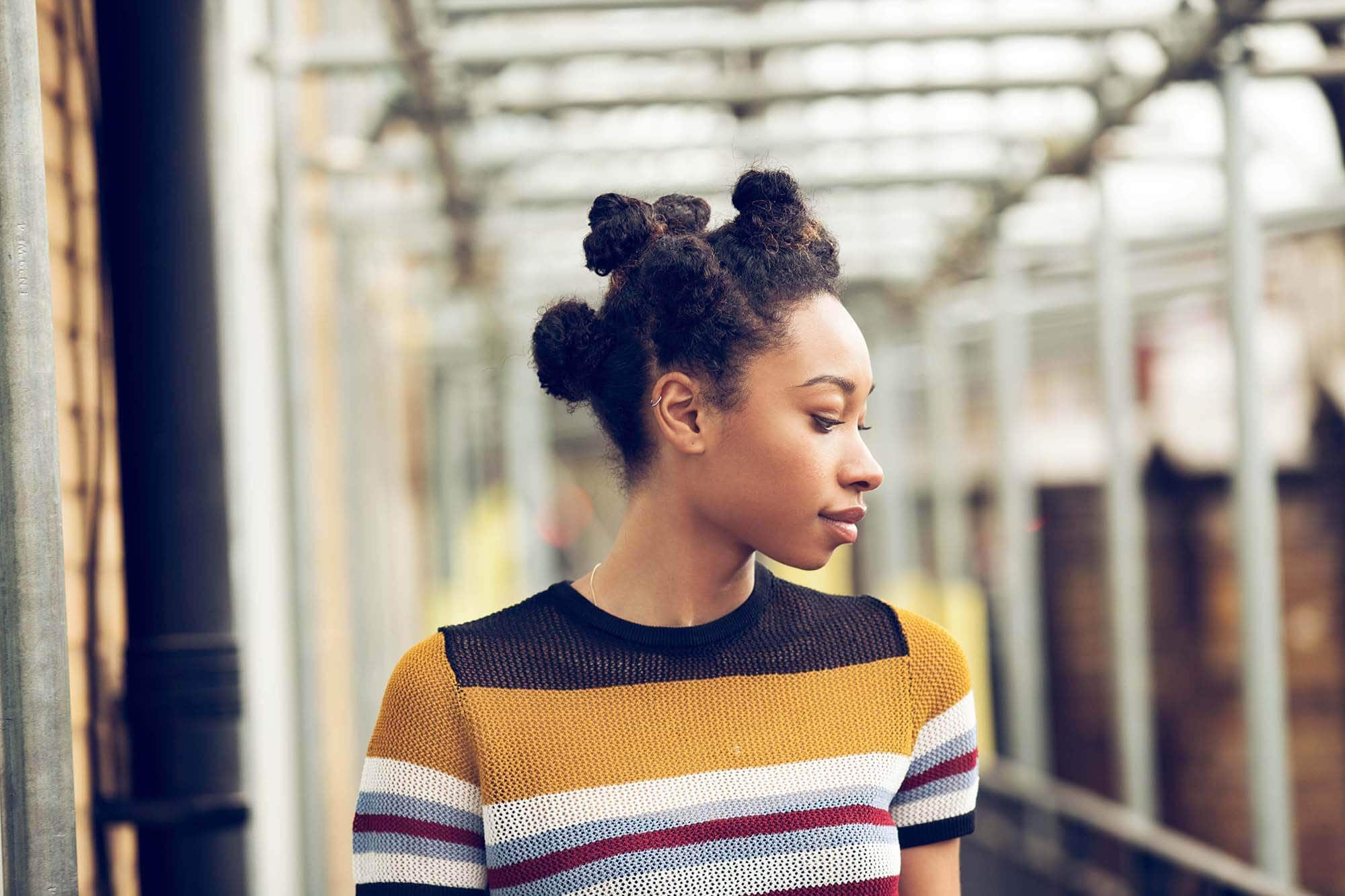 black women hairstyles: close up shot of a woman with chocolate brown natural hair styled into bantu knots, wearing a striped shirt and posing outside