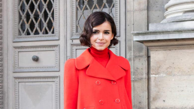 a short hair girl smiling outside while wearing red coat