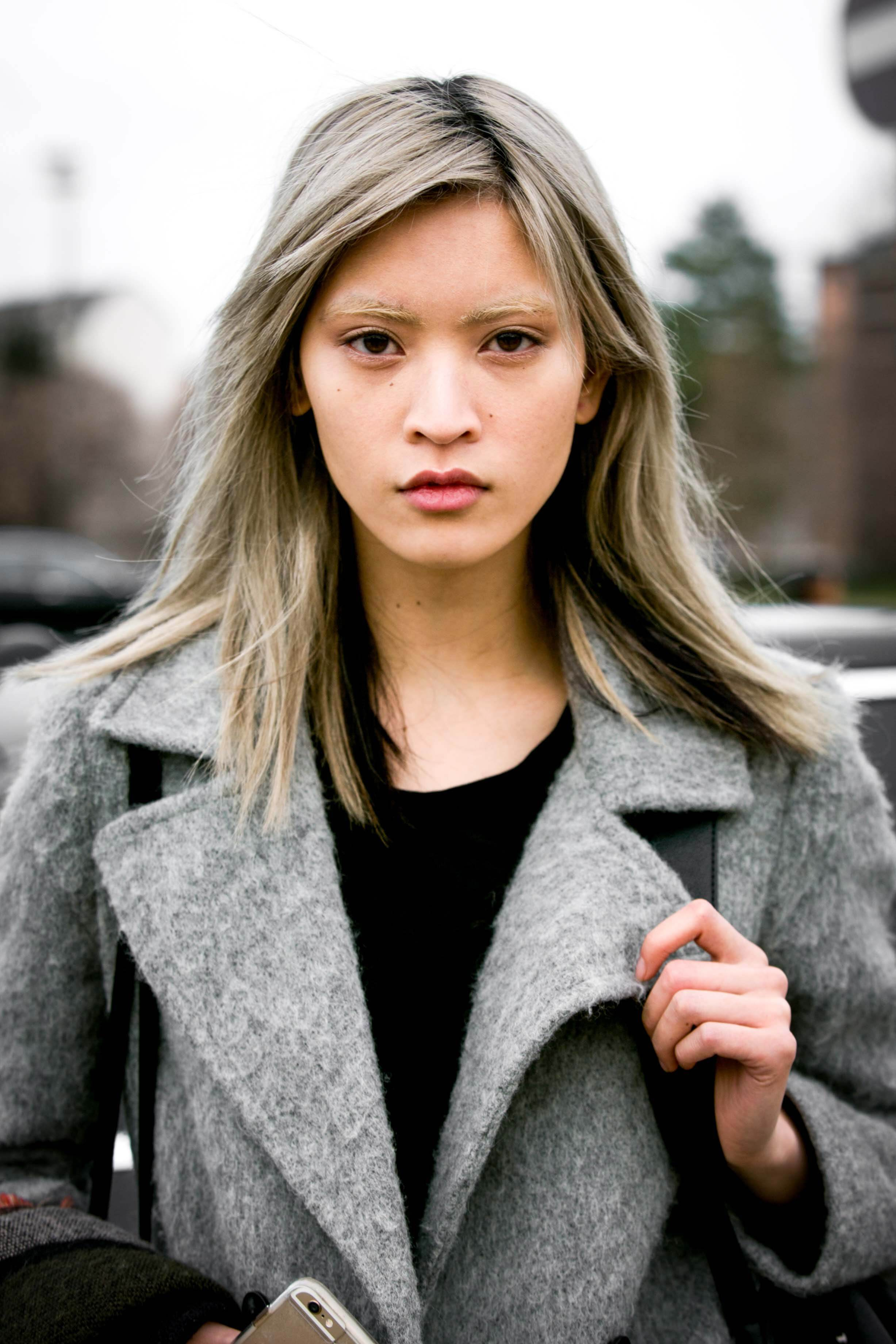 Silver shampoo: Fashion week street style picture of an Asian model with shoulder length straight grey hair.