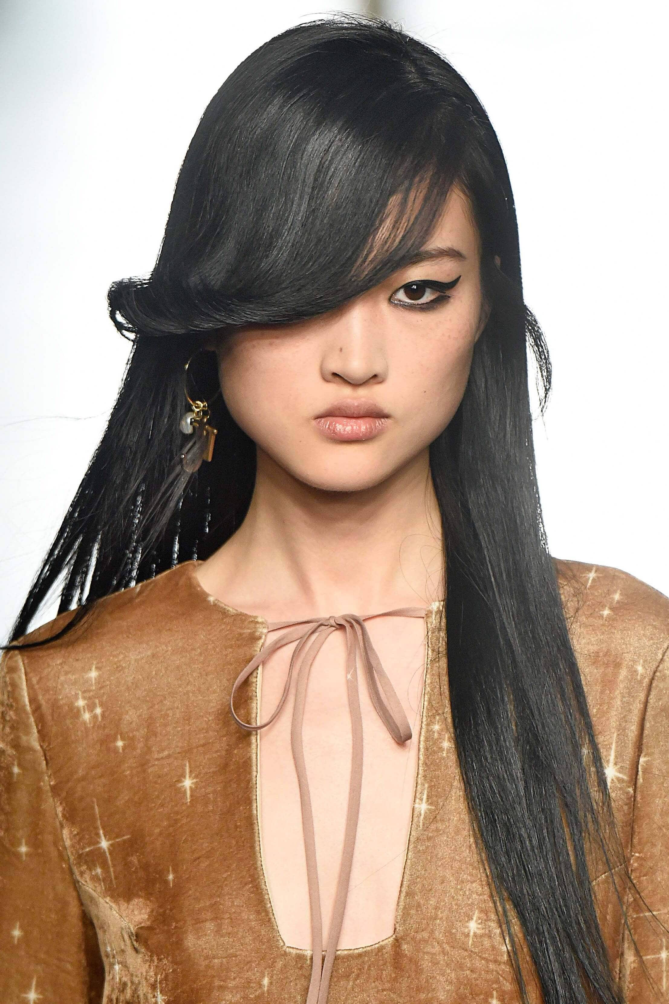 Asian woman with long hair and side swept bangs: hairstyles for round faces