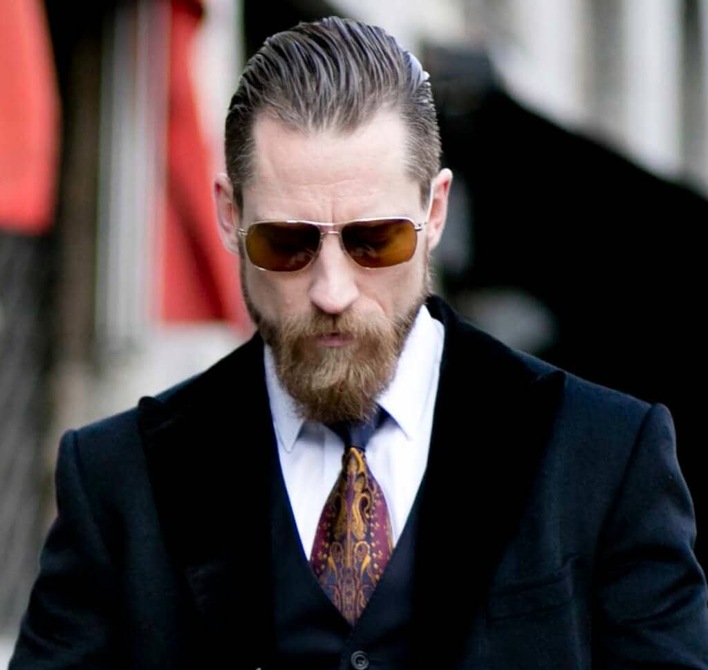 front view of a man with a beard and brown hair slicked back