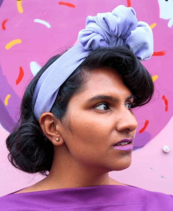 Woman with short hair with drop waves bob and a faux fringe wearing a purple headband