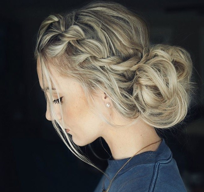 Updos with braids: Close up shot of a woman with rope twisted braid into a low bun.