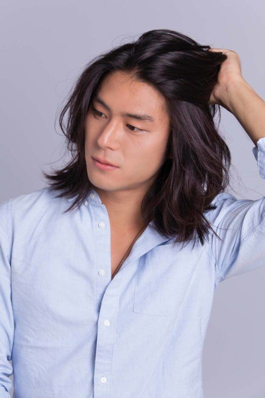 Asian man bun: Asian male model with shoulder-length hair touching his hair