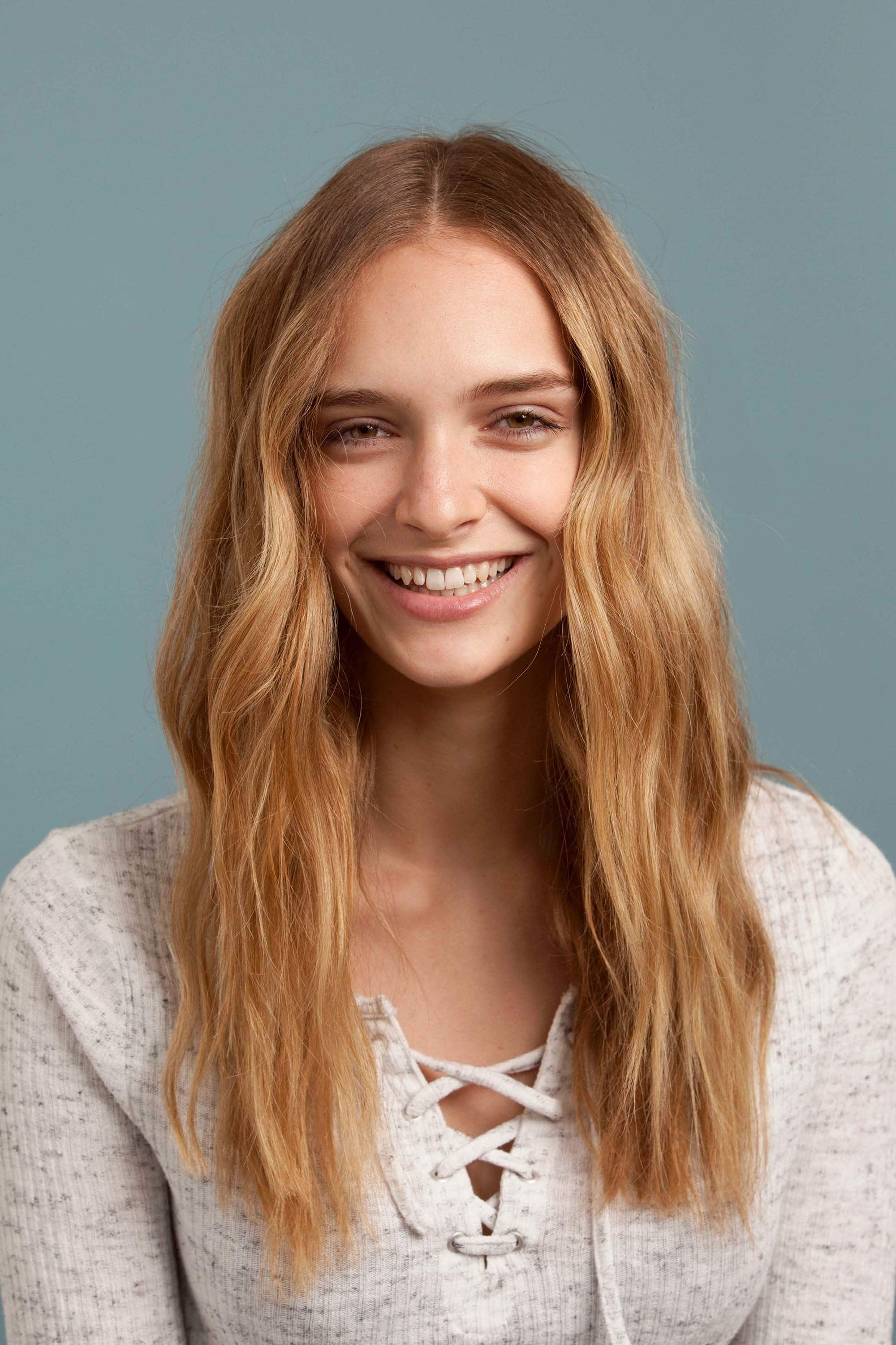 How to use a curling wand: Blonde model with mid-length, softly waved hair, wearing a lace-up top