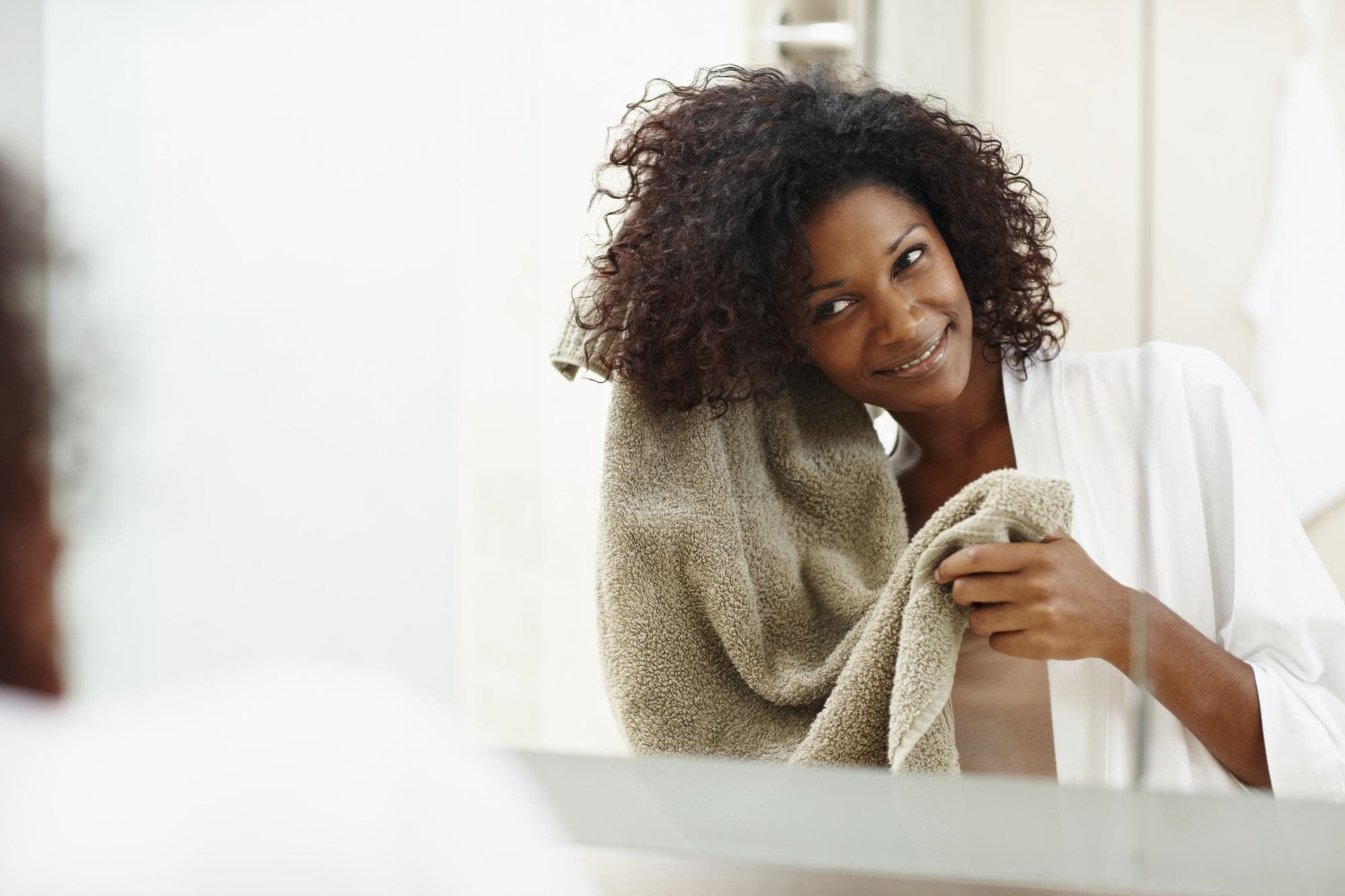 black woman with afro hair towel drying her hair in the mirror