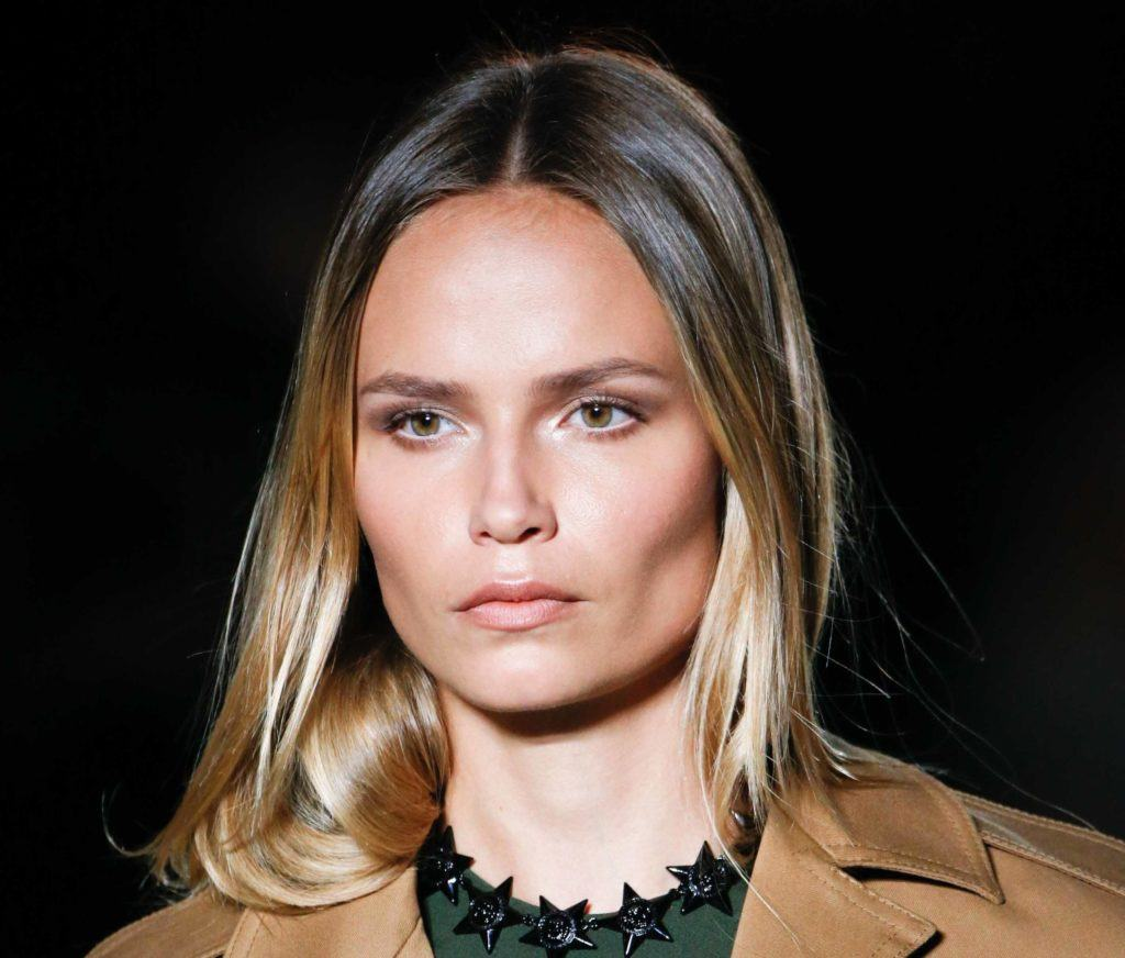 front image of a woman with ombre dark blonde hair worn down