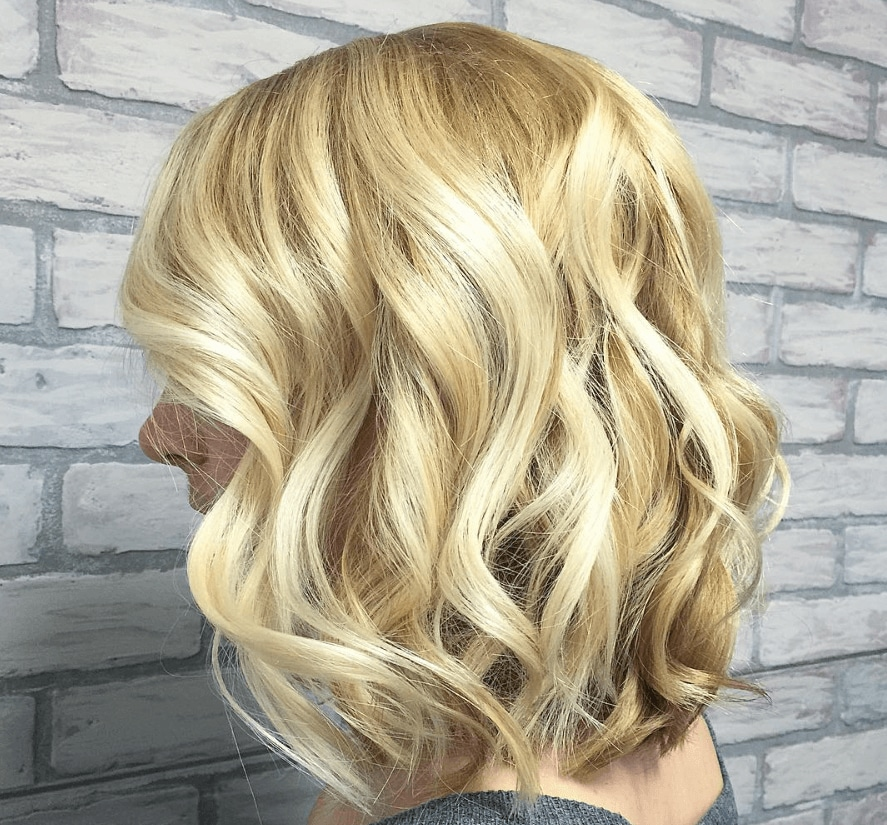 side view of a woman's hair with blonde waves in a blonde bob