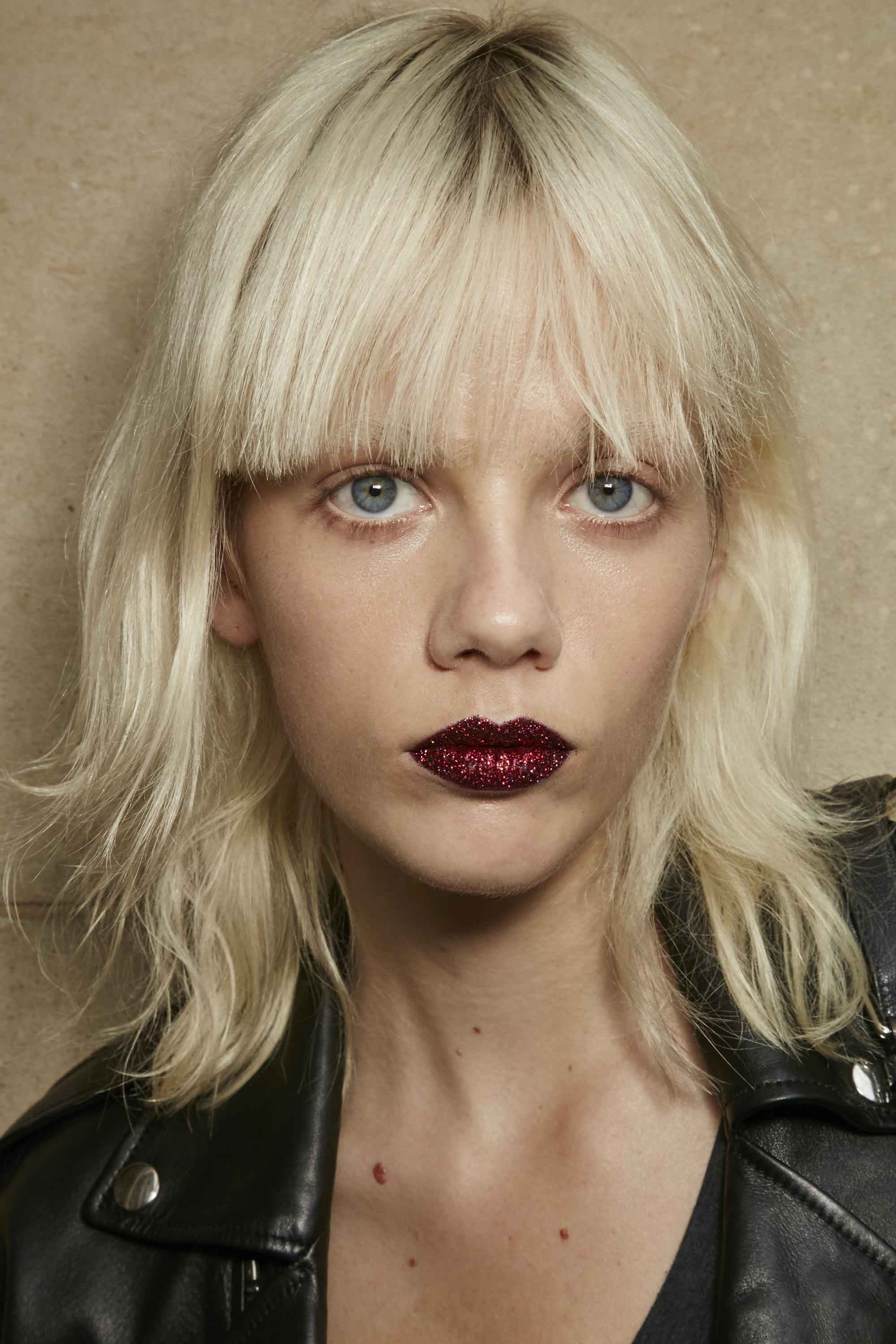 model with platinum blonde hair cut into a short shag haircut and blunt bangs, wearing dark red lipstick