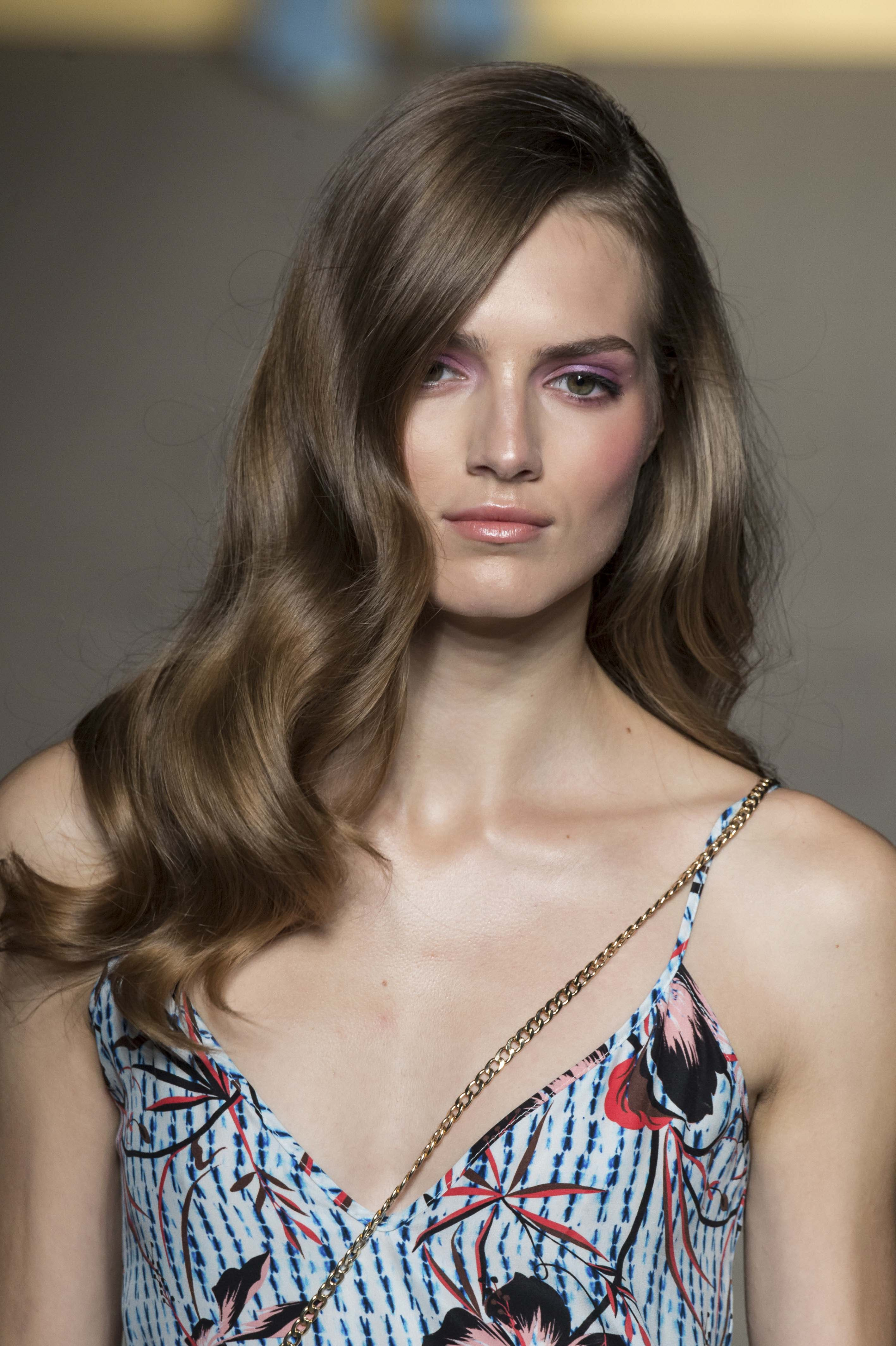 Curly prom hairstyles: Medium brown haired model at Matthew Williamson SS15 with a glam wavy hairstyle