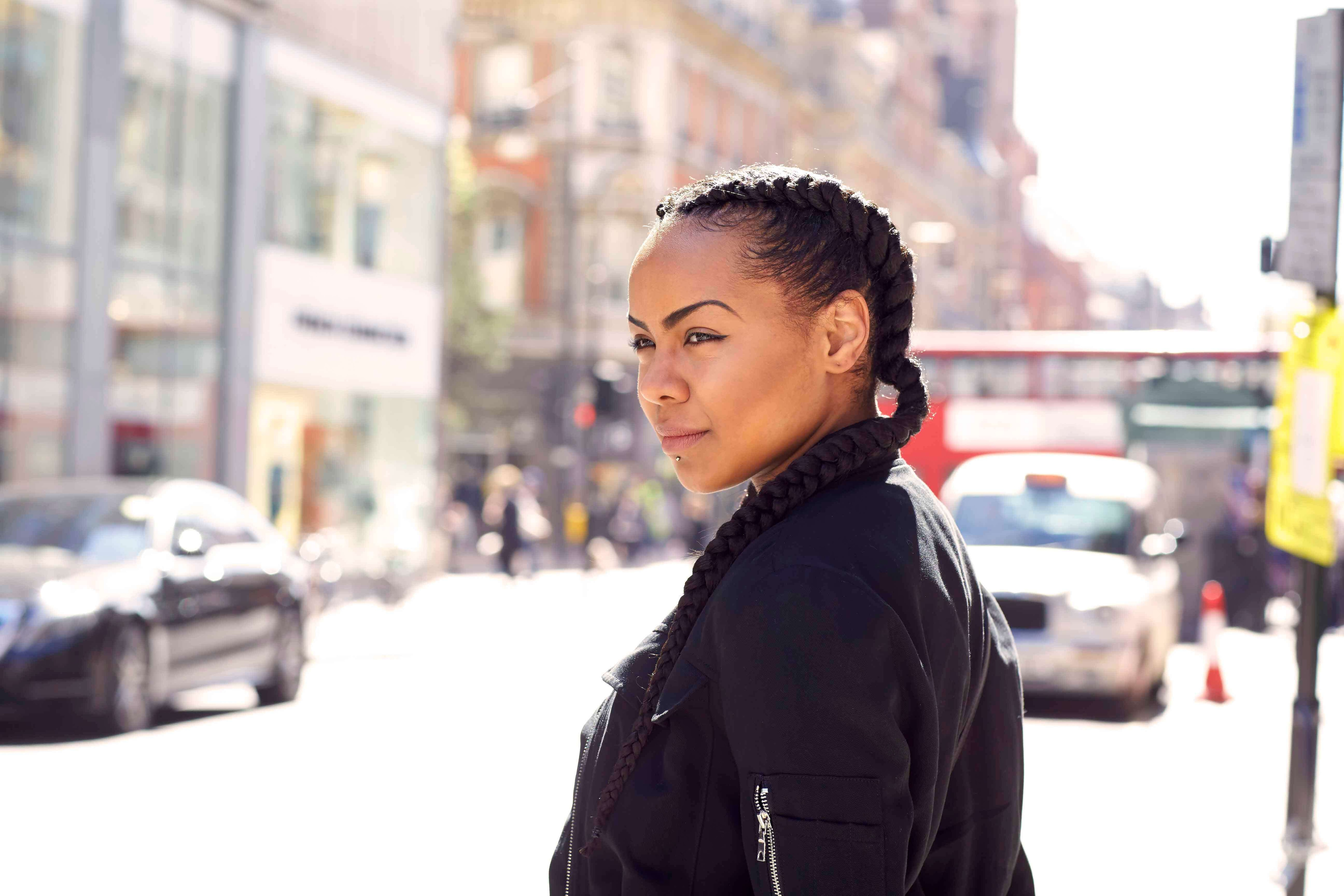 street style shot of a girl in the street wearing a black bomber jacket with her natural hair in boxer braids